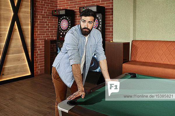 Portrait of man at billiard table