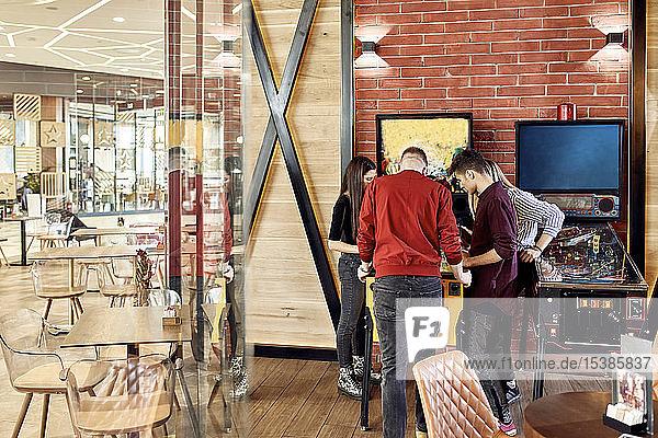 Friends standing around pinball machine