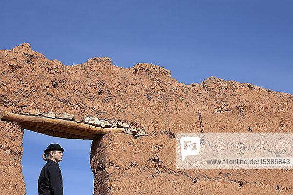 Morocco  Ait-Ben-Haddou  man wearing a bowler hat under loam wall