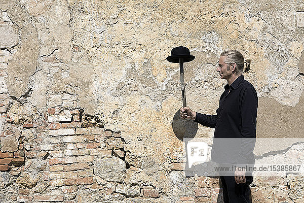 Man standing at stone wall balancing a bowler hat on a stick