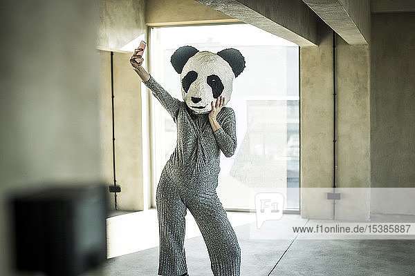 Woman with panda mask standing in office  taking selfie