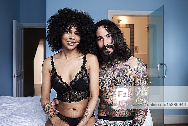 Porträt eines lächelnden jungen Paares auf dem Bett sitzend
