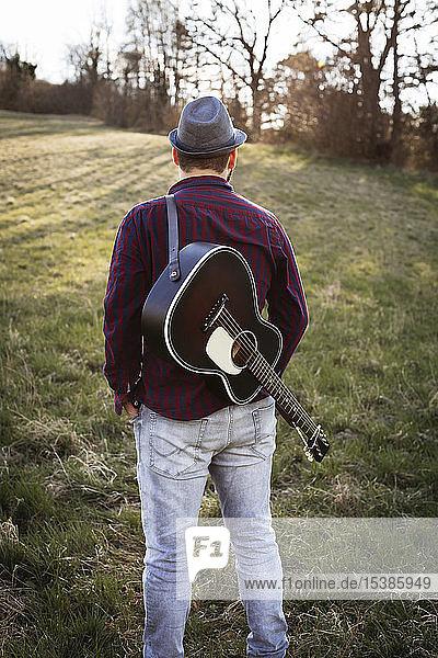 Rückansicht eines auf einer Wiese stehenden Mannes mit Gitarre