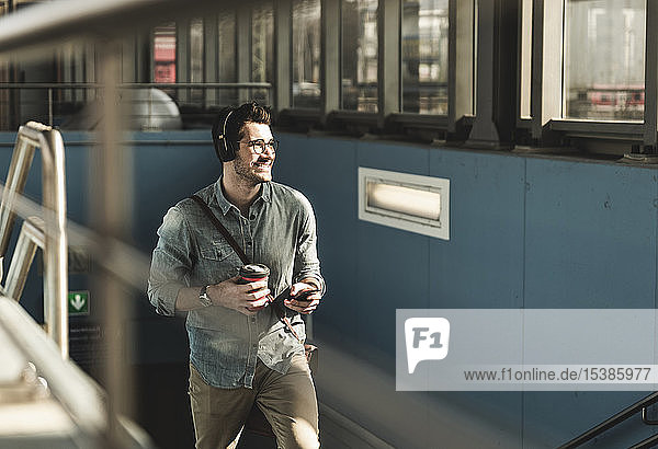 Smiling young man with headphones  cell phone and takeaway coffee walking at the station