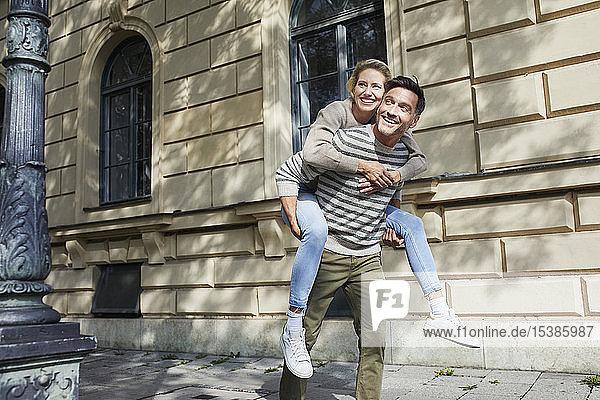 Glücklicher Mann nimmt Frau huckepack auf dem Bürgersteig in der Stadt mit