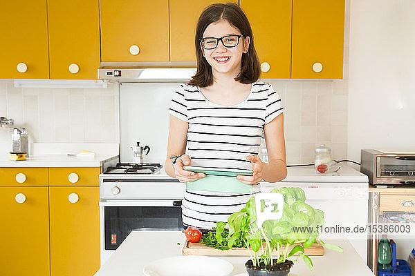 Porträt eines in der Küche stehenden lächelnden Mädchens mit Tablette