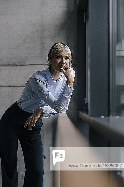 Confident businesswoman standing at window  thinking