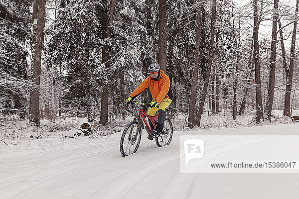 Man riding mountainbike on path in winter forest