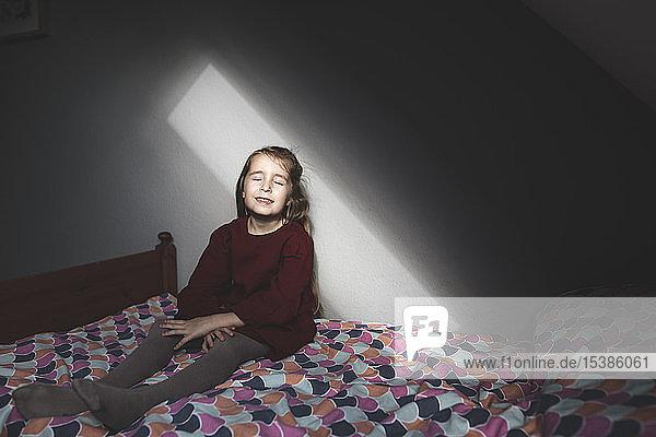 Lächelndes Mädchen sitzt zu Hause mit geschlossenen Augen auf dem Bett