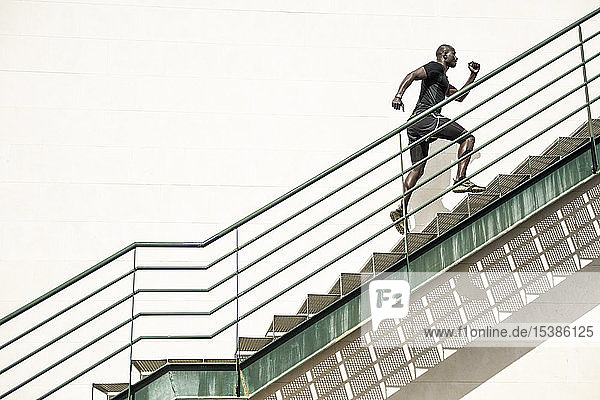 Man in black sportswear running up staircase