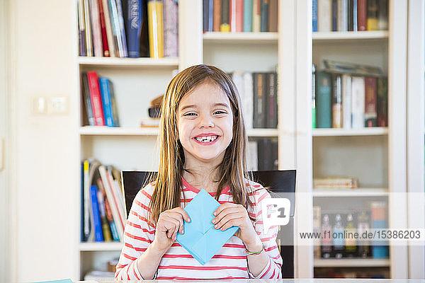 Porträt eines glücklichen Mädchens  das zu Hause am Papier bastelt