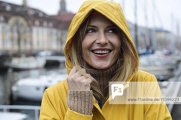 Dänemark  Kopenhagen  Porträt einer glücklichen Frau im Stadthafen bei Regenwetter