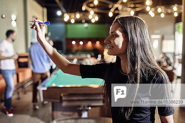 Smiling young woman playing darts