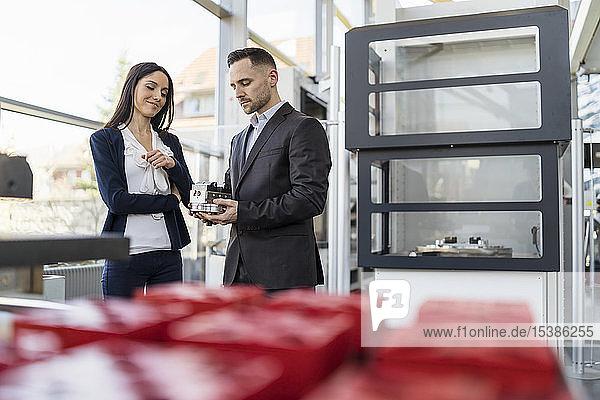 Geschäftsmann und Geschäftsfrau betrachten Werkstück in Fabrik