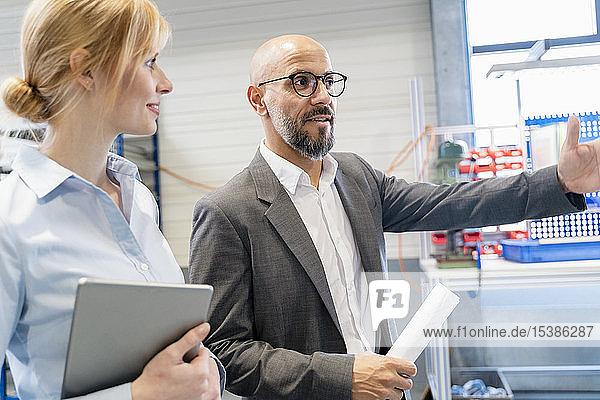 Geschäftsmann im Gespräch mit Geschäftsfrau in Fabrik