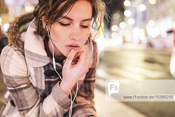 Spanien  Madrid  junge Frau in der Stadt  die nachts Kopfhörer trägt