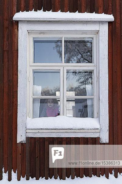 Finnland  Kuopio  kleines Mädchen  das im Winter aus dem Fenster eines Bauernhauses schaut