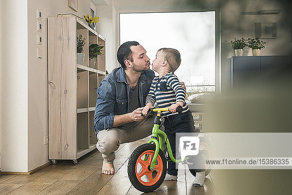 Father kissing son with a balance bicycle at home