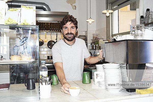 Porträt eines lächelnden Barista an der Theke eines Cafés