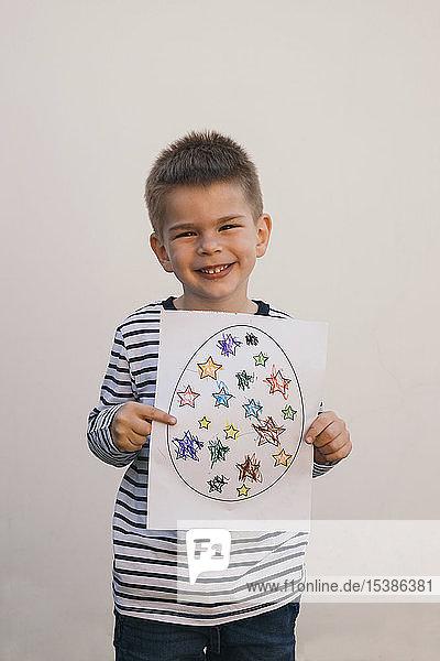 Junge hält sein Kunstwerk und lächelt