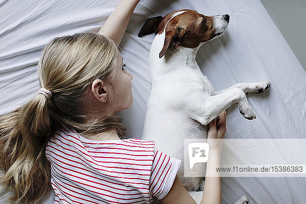 Blondes Mädchen liegt auf Bett und kitzelt ihren Hund