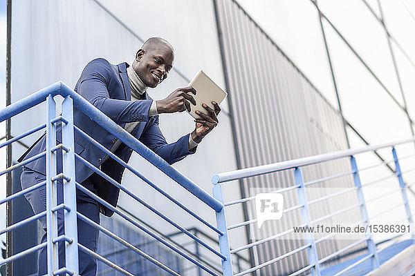Portrait eines lächelnden Geschäftsmannes mit digitalem Tablet im Freien