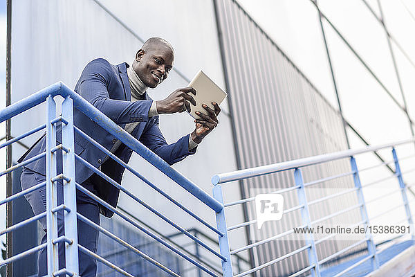 Portrait of smiling businessman using digital tablet outdoors