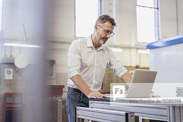 Geschäftsmann mit Laptop in der Fabrik