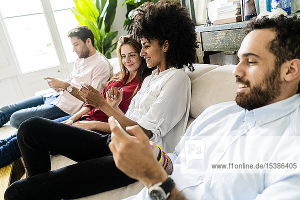 Friends sitting on couch  working casually together  using smartphones