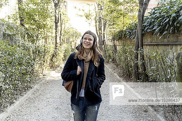 Junge Frau  die in der Stadt spazieren geht und mit Kopfhörern Musik hört