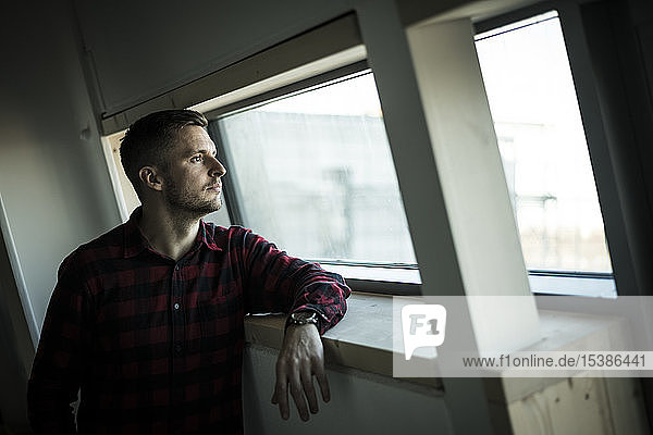 Young man looking out of window  daydreaming