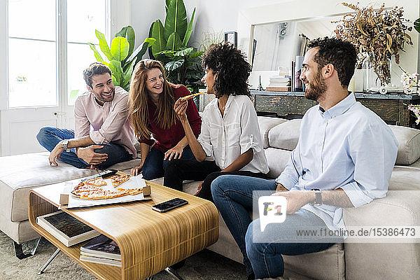 Freunde  die Spaß haben  zusammen Pizza essen  auf der Couch sitzen