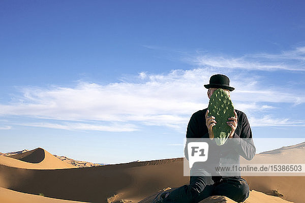 Morocco  Merzouga  Erg Chebbi  man wearing a bowler hat holding cactus leaf in front of his face in desert dune