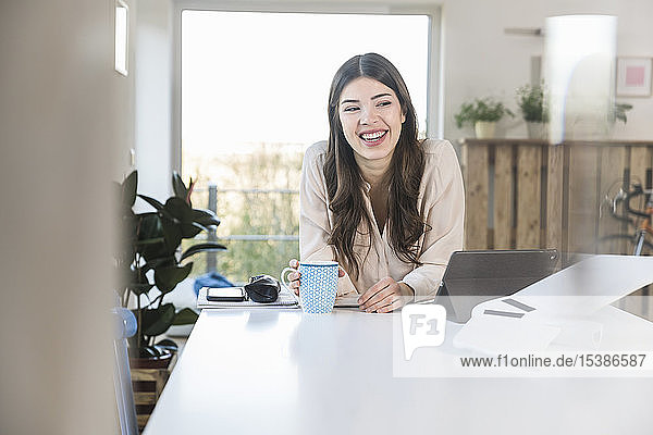 Happy young woman sitting at table at home