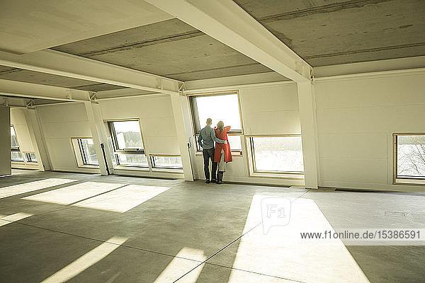 Ehepaar schaut aus dem Fenster seines neuen Zuhauses