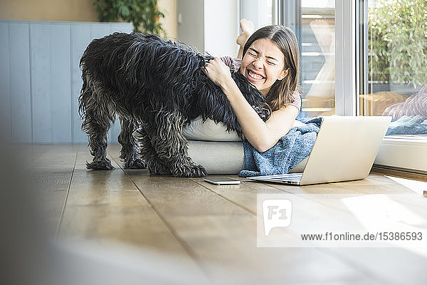 Happy young woman with dog lying at the window at home