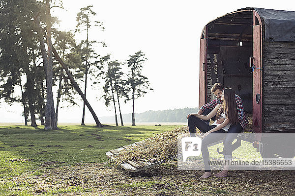 Happy young couple sitting on trailer in the countryside