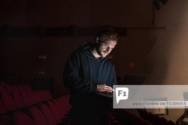 Regisseur steht mit Laptop im Theatersaal