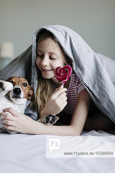 Lächelndes Mädchen liegt auf dem Bett mit einem Lolli  der ihren Hund kitzelt