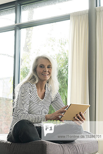 Portrait of happy mature woman using digital tablet at home