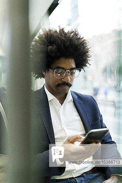 Spain  Barcelona  businessman in a tram using cell phone