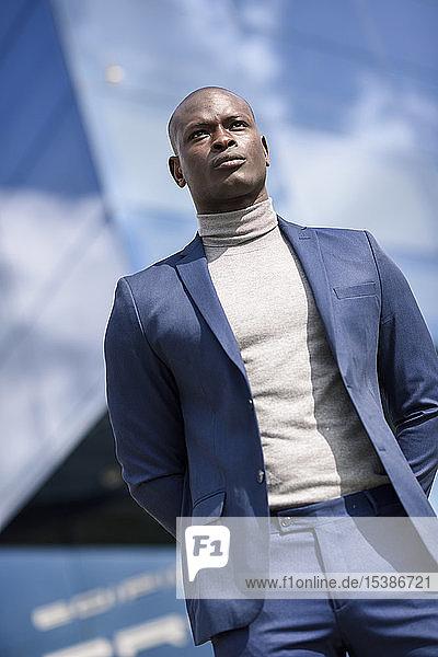 Porträt eines Geschäftsmannes in blauem Anzug und grauem Rollkragenpullover