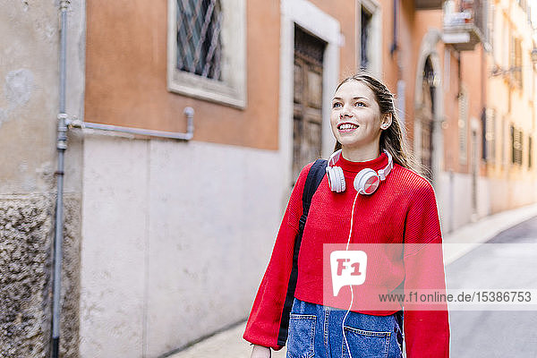 Young woman wearing red pullover  headphones in Verona