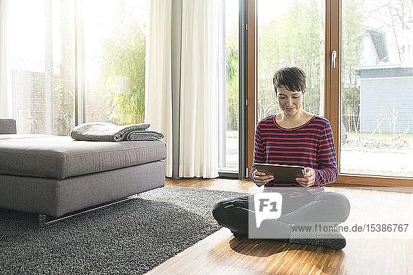 Porträt einer Frau  die mit einem digitalen Tablett auf dem Boden eines Wohnzimmers sitzt