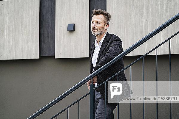 Porträt eines nachdenklichen  reifen Geschäftsmannes  der sich an ein Geländer lehnt