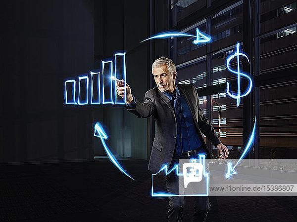 Geschäftsmann malt Wirtschaftskreislauf mit Licht