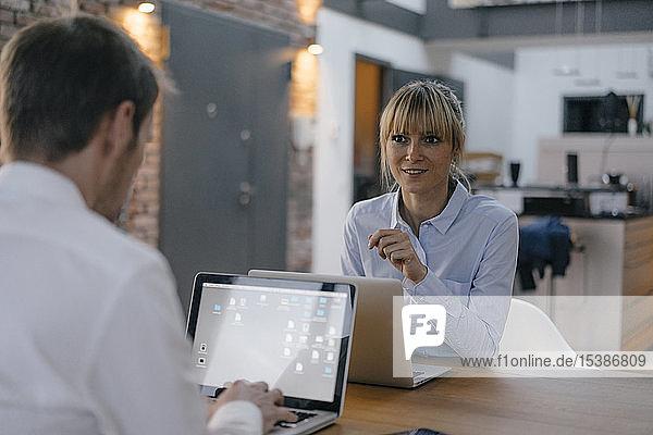 Geschäftsmann und -frau sitzen am Schreibtisch und arbeiten am Laptop
