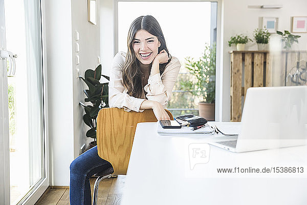 Portrait of happy young woman sitting at table at home