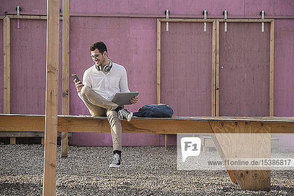 Smiling young man sitting on platform using cell phone