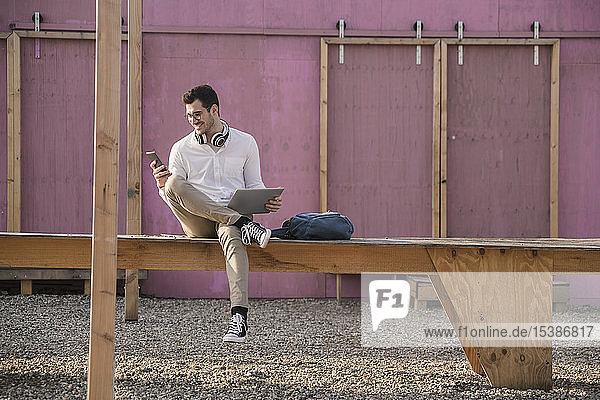 Lächelnder junger Mann sitzt auf Bahnsteig und benutzt Handy